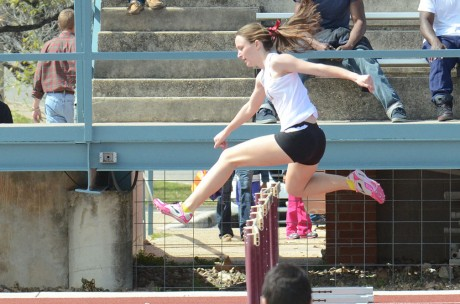 Junior distance runner Jessie Dean jumps over a hurdle during the 4x400 meter relay. The women's time puts them fifth in all-time record books. Photo by Megan McLoughlin.