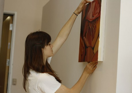 """Senior Jennifer Lewish hangs a painting in preparation for the opening of """"Kunstkammer,"""" the 2013 senior art show which will open at 5 p.m. Thursday, April 25, in the Michael and Noémi Neidorff Art Gallery in the Dicke-Smith Art Building. Photo by Sarah Cooper."""