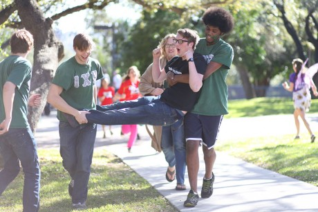 Sophomores and members of Iota Chi Rho Clayton Ford and Darin Feagins carry first-year William Freeman toward Miller Fountain for his honorary dunk in the water, as per Bid Day tradition. Photo by Anh-Viet Dinh.