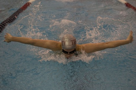 photo courtesy of James Shultz. Senior Mary Price competes in the 100-meter butterfly during the conference meet Feb. 13-16. Price set a school record in this event.