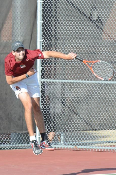 First year Connor Dunn fires the ball at his opponents during a doubles match with John Hopkins University on Wednesday. Photo by Sarah Cooper.