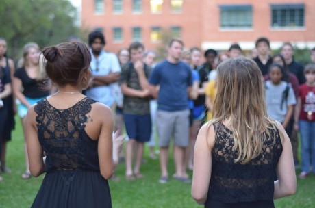 First years Sydney Wright and Hayley Says, friends of Sheena, talk about her love of music, horseback riding and travel, as members of the community look on during the memorial held at 8 p.m. on Tuesday. Photo by Matthew Brink.